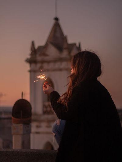 Women holding sparkler sitting against sky during sunset