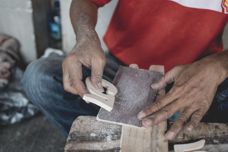 Midsection of man making number 5 of wood