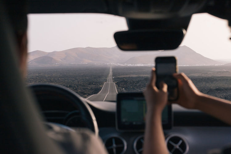 Rear view of photographing using mobile phone in car