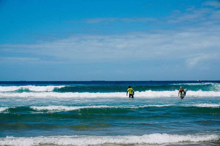 Rear view of friends with surfboards walking in sea against sky