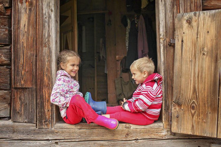 Happy girl sitting on wood