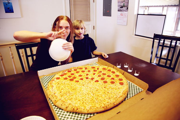Portrait of happy siblings with pizza at table