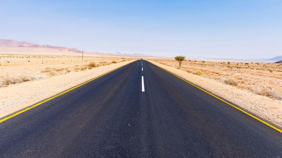 Road amidst desert against clear sky