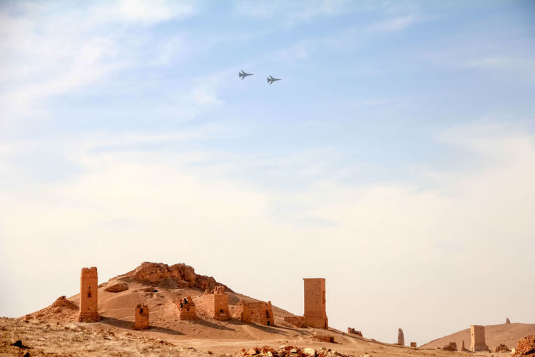 The Syrian Air Force monitors Palmyra. ASIA Ancient Archeology Castle Desert East MIG-21 Palmyra Ruins Syria  Airforce Arabic Army Aviation Battle Buildings Civilization Culture Defense Engine Flight Forces Hill History Military Airplane Old Ruin