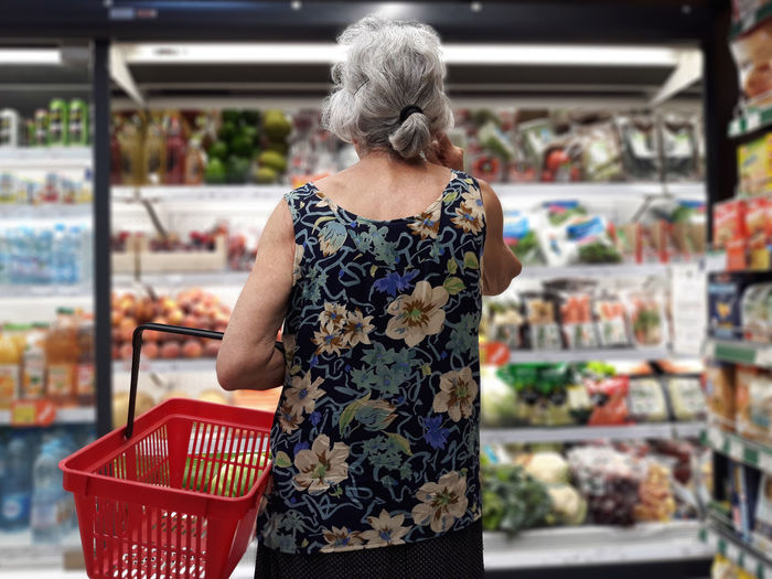 Shopping Adult Buying Choice Consumerism Elderly Woman Floral Pattern Food Food And Drink Fruit Groceries Lifestyles Market One Person Rear View Retail  Retail Display Shopping Shopping Basket Standing Store Supermarket Variation Vegetables Women