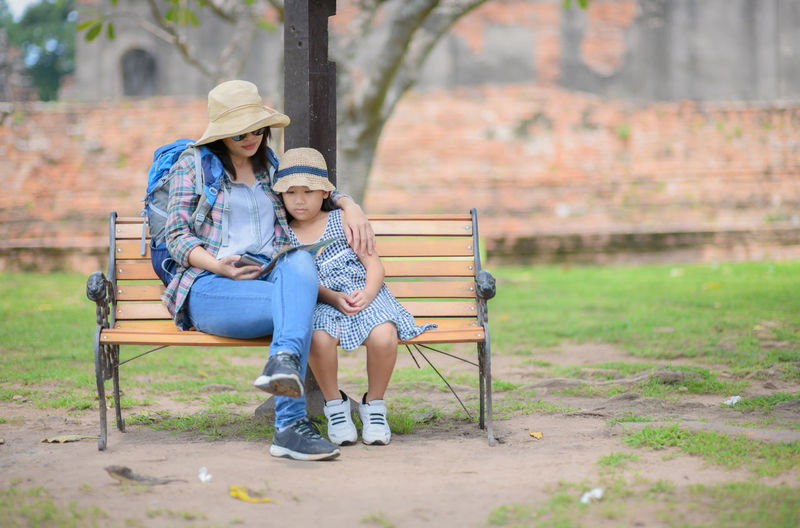 Full length of mother and daughter sitting on bench at park