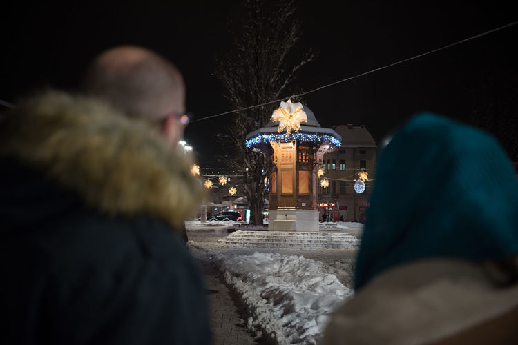 Night Illuminated Winter Real People Cold Temperature Rear View Architecture Motion People Lifestyles Leisure Activity City Snow Street Selective Focus Built Structure Nature Women Adult Building Exterior Warm Clothing Hood - Clothing Sarajevobosnia Sarajevo Balkans Europe