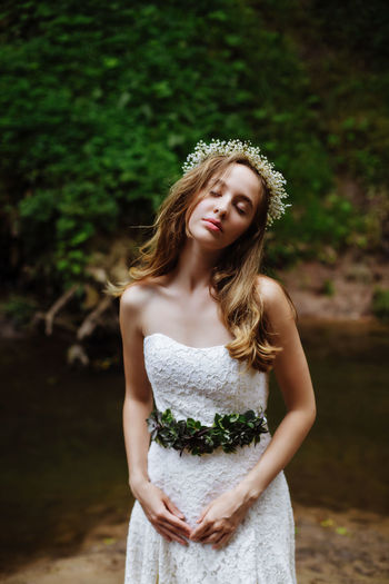 Beautiful young bride with eyes closed standing in forest