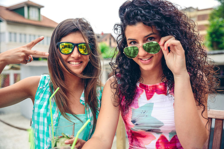 Close up of two happy young women with sunglasses smiling and looking at camera while holding green vegetable smoothies outdoors Cocktail Fiends Friends Happiness Happy Horizontal Juice Sitting Young Caucasian Cheerful Drink Enjoy Friendship Leisure Lifestyles Outdoors Party People Real People Smoothie Straw Summer Togheter Women