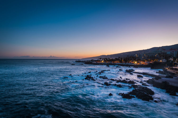 PUERTO DE LA CRUZ, TENERIFE / SPAIN - FEBRUARY 24 2018: View on bay of Puerto de la Cruz in the morning Beach Beauty In Nature Clear Sky Copy Space Idyllic Illuminated Land Motion Nature No People Outdoors Scenics - Nature Sea Sky Sunset Tranquil Scene Tranquility Water Waterfront