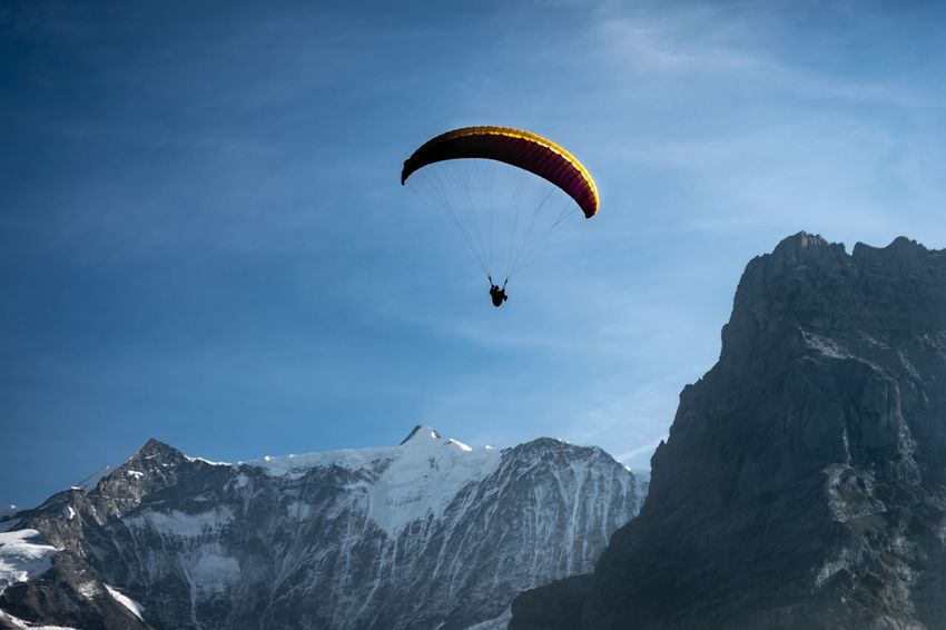 extreme sports paragliding in front of snowcapped mountains, Swiss Alps, Bernese Oberland, Switzerland Leisure Activity Sky Extreme Sports Paragliding Parachute Cloud - Sky Swiss Alps Alpine Alps Snowcapped Mountain Peak Summit Jumping Travel Mountain Alpen Berge Holiday Vacations Activity Action People Snow Blue Sky Sport EyeEmNewHere Autumn Mood