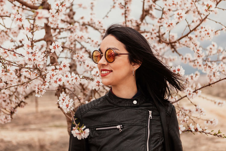 Beautiful young woman standing by cherry blossom tree