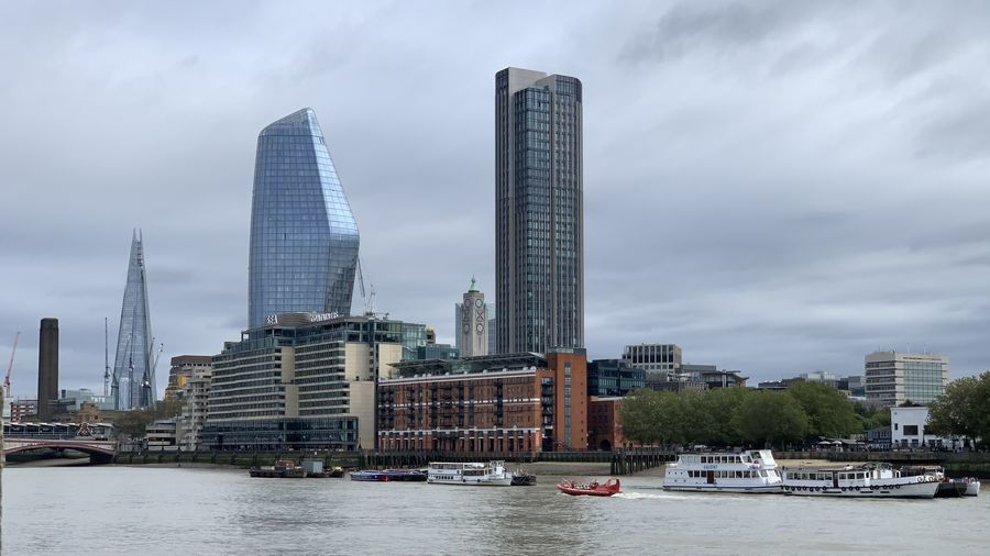 Modern buildings by river against sky in city