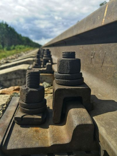 Close-up of railroad track against cloudy sky