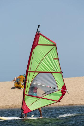 Traditional windmill on beach against clear sky