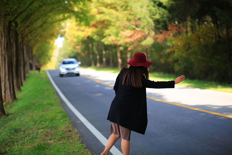 Rear view of woman hitchhiking on road