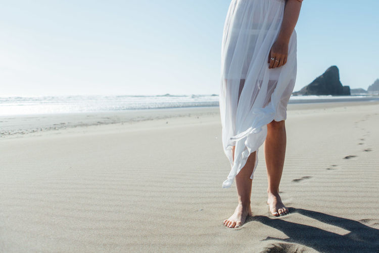Low Section Of Young Woman Standing On Beach