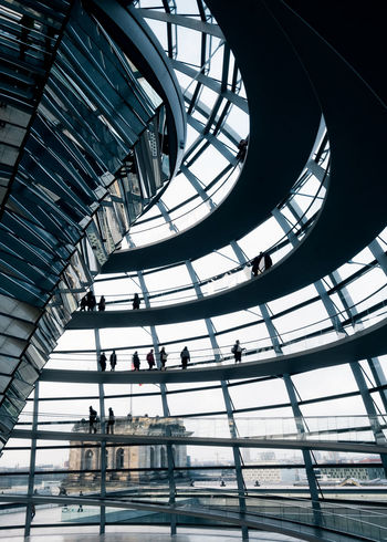 People wandering around the iconic German Reichstag building. Architecture Berlin German Parliament Landmarks Modern Architecture ReichstagBuilding Architecture Built Structure Copula Curved Architecture Day Dome Glass Glass Dome Glass Windows Indoors  Landmark People People Walking  Reichstag The Reichstag