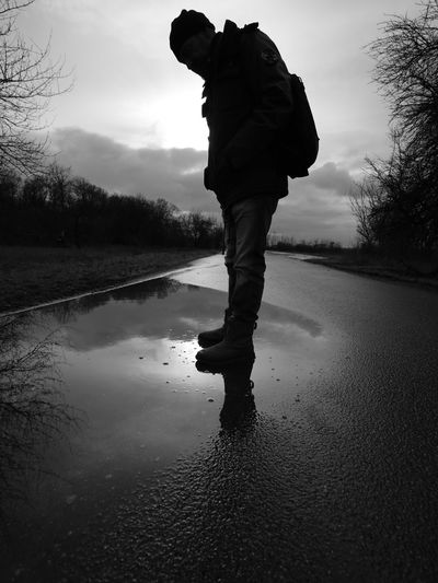 Rear view of man standing on road against sky