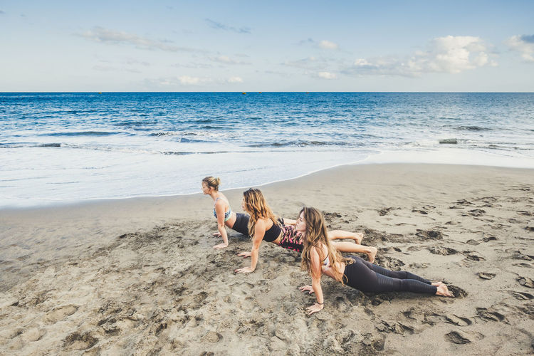 Women doing plank at beach against sky