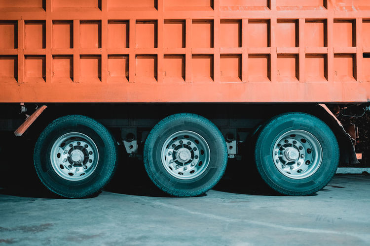 Construction Heavy Duty Industry Business Freight Transportation Heavy Equipment In A Row Industry Lorries Metal Orange Color Parking Road Robust Semi-truck Stationary Tire Transportation Travel Truck Wheel Wheels