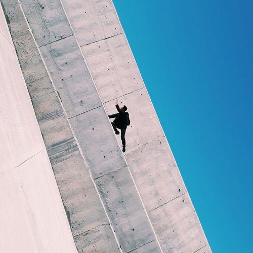 Tilt image of man on retaining wall