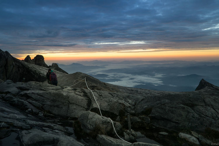 Friends hiking on mountain peak against cloudy sky during sunset