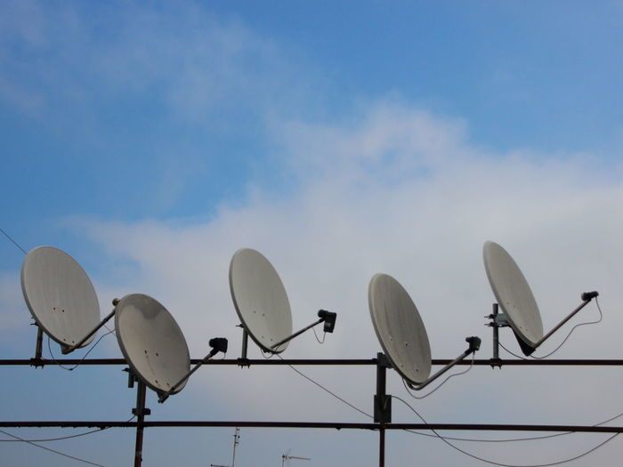 Low angle view of satellite dishes against sky