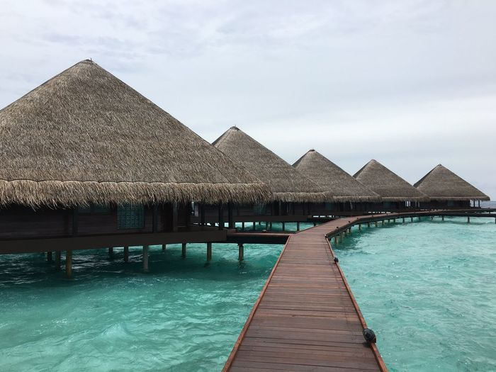 Thatched roof huts on pier against cloudy sky