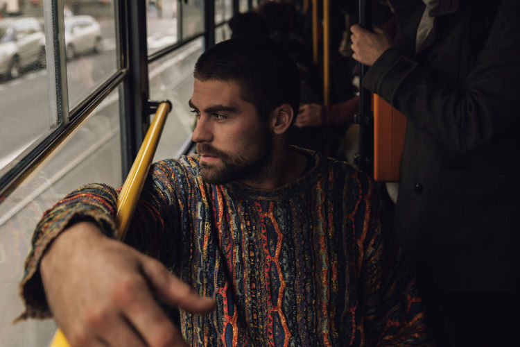 Young man looking away while sitting in bus