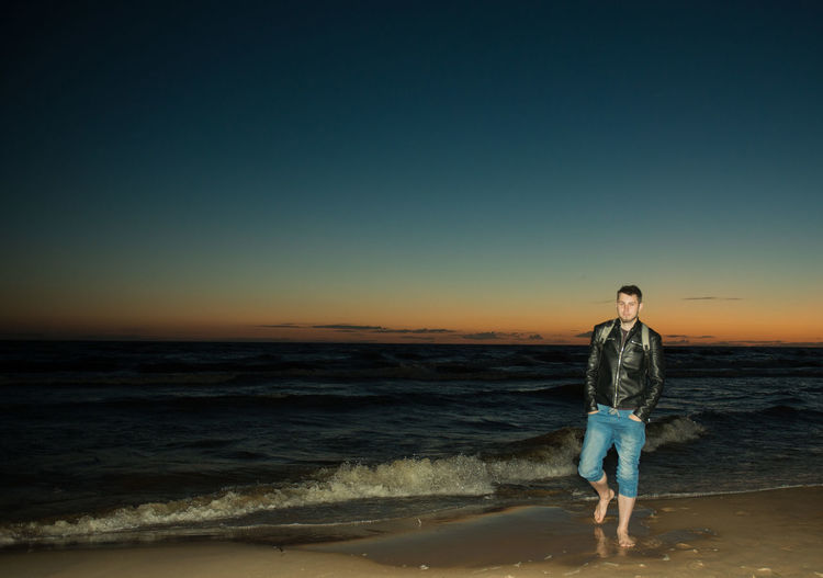 Young man walking on shore at beach against sky during sunset