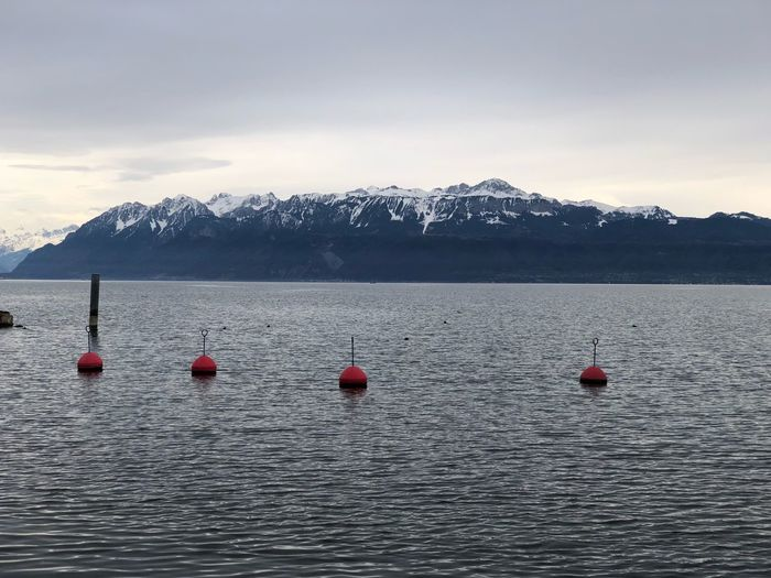 Buoys in lake against sky during winter