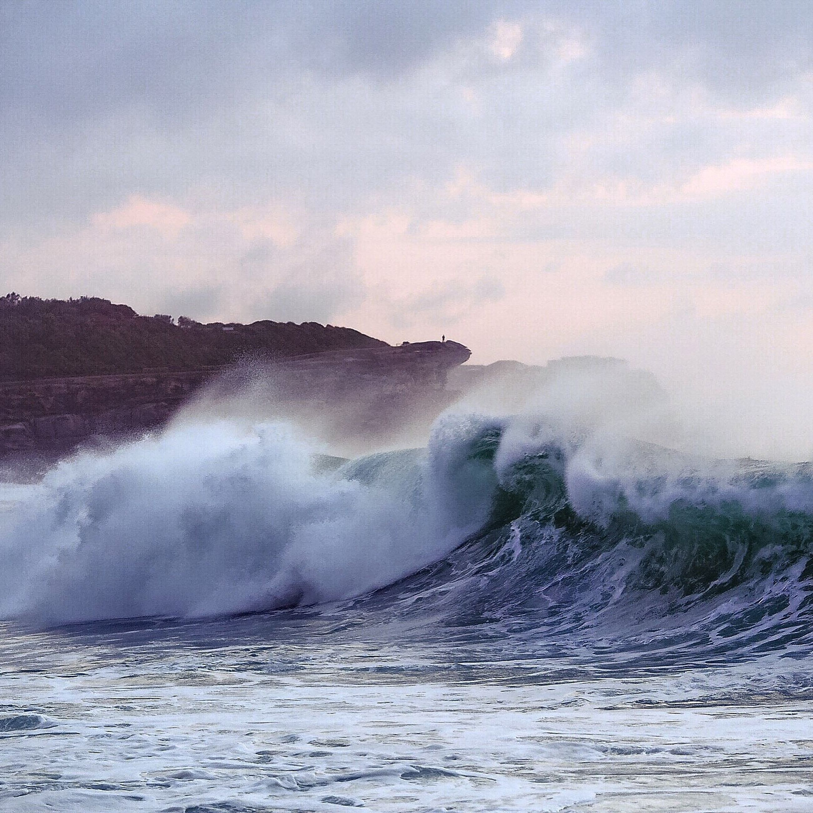 water, sea, scenics, beauty in nature, power in nature, surf, motion, waterfront, wave, nature, sky, splashing, tranquil scene, tranquility, idyllic, cloud - sky, outdoors, non-urban scene, geology, mountain