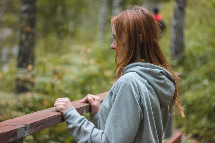 Side view of young woman looking away in forest