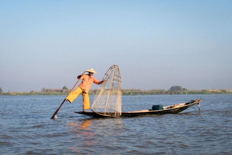 Balance Balancing Act Burma Day Fisherman Fishing Fishing Boat Fishing Net Fishing Tools Hat Inle Lake Lake Myanmar Nature Net Occupation Orange Clothes Outdoors People Sky Tradition Traditional Clothing Water