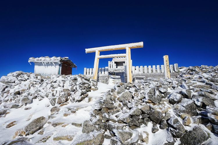 Low angle view of snow covered rocks against clear blue sky
