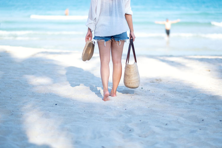 A woman holding bag and shoes while strolling on the beach with the sea and blue sky background Adult Asian  Attractive Back Background Bag Beach Beautiful Beauty Blue Clouds Coast Female Fresh Girl Happy Hat Holding Holiday Lady Leisure Lifestyle Look Nature Ocean Outdoor People person Relax Relaxation Sand Sea Shoes Sky Space Standing Stroll Strolling Summer Sun