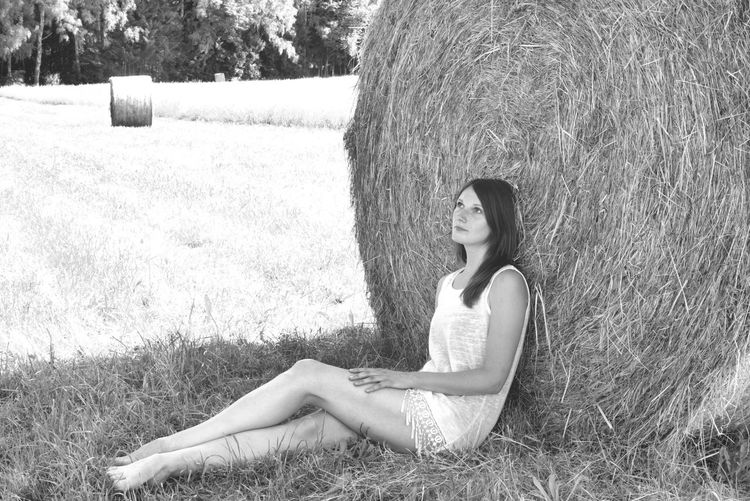Thoughtful Woman Leaning On Hay Bale While Sitting At Farm Field