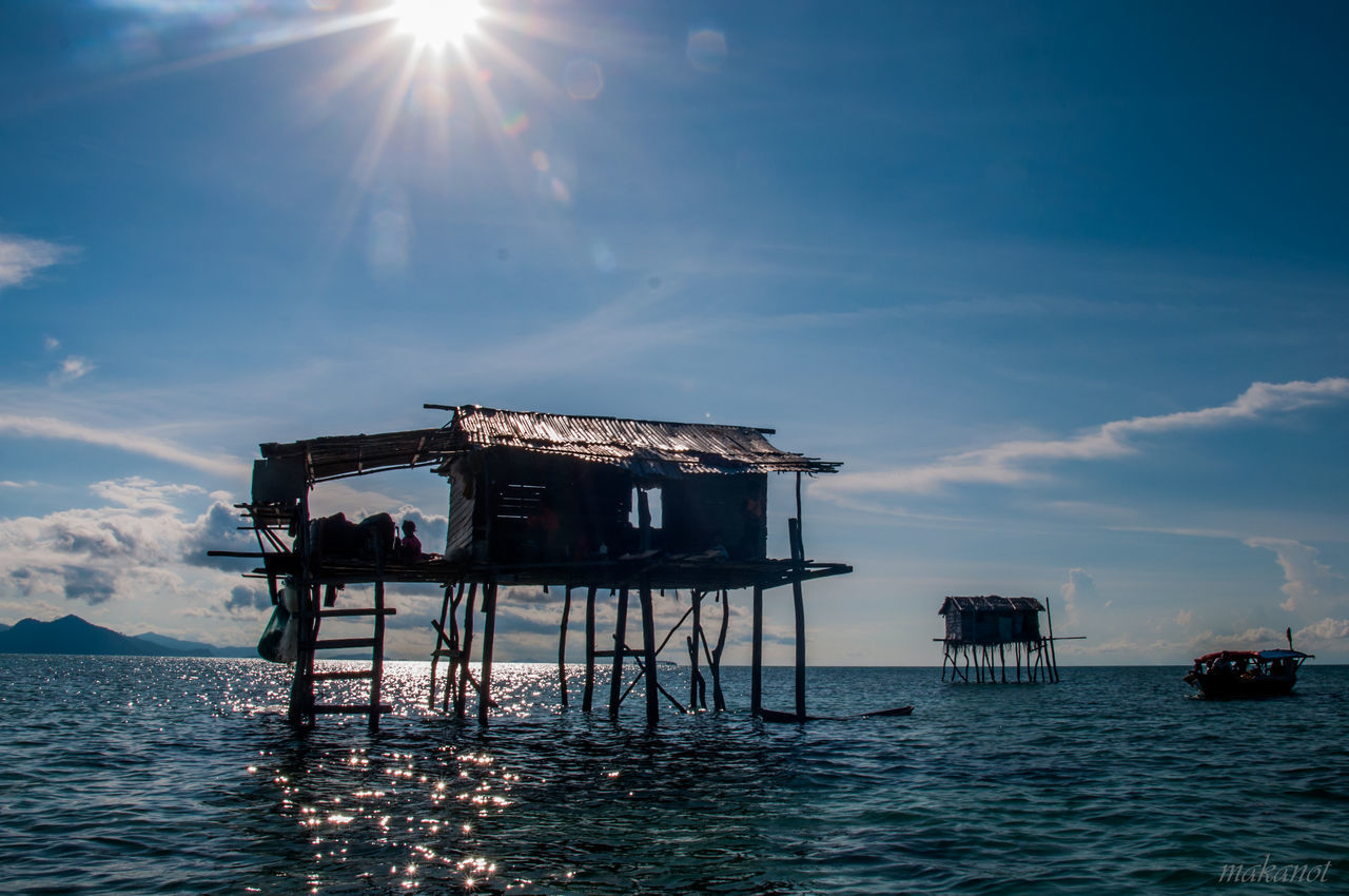 architecture, built structure, water, sunlight, sky, sea, stilt, stilt house, tranquility, outdoors, nature, day, no people, building exterior