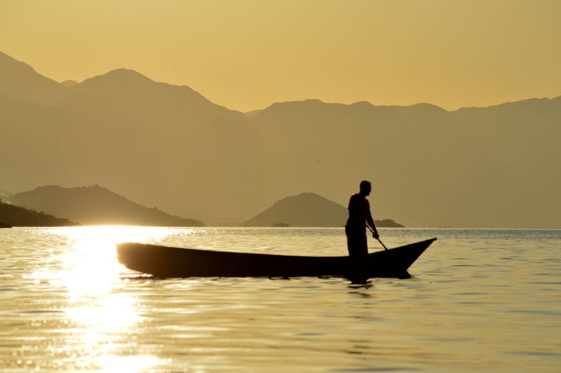 Silhouette man in boat on lake against sky during sunset