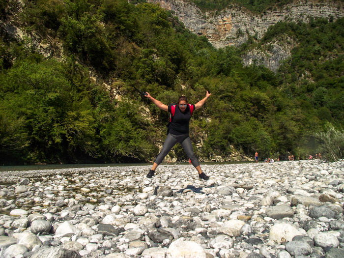 Full Length Of Woman Jumping Over Rocks