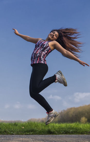 Jump Arms Raised Freedom Jumping Jumping Gir Long Hair One Person Playing Girl Tousled Hair Wind