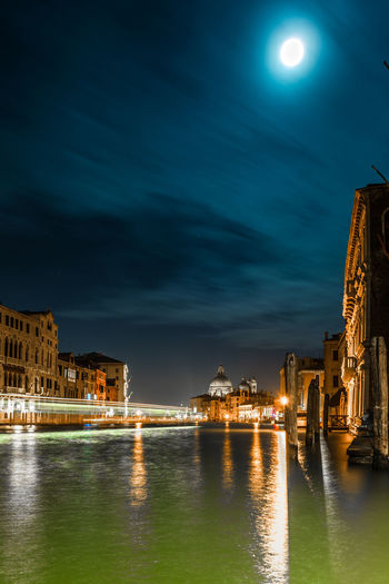 Illuminated buildings by grand canal during night