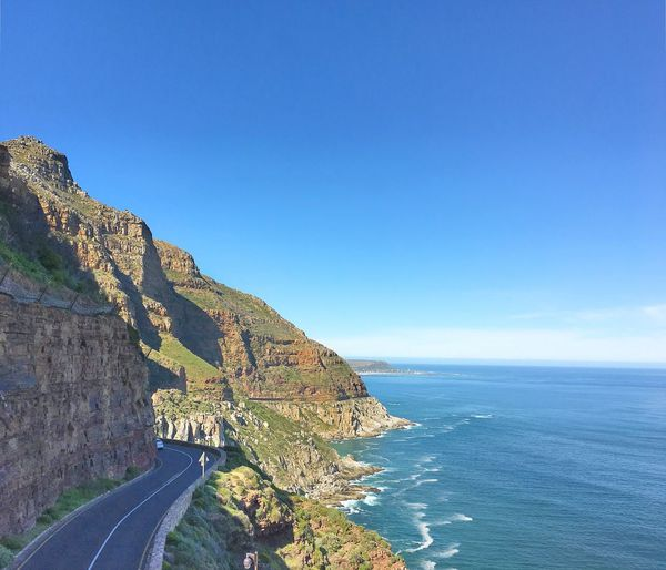 Coastal road by cliff and sea against blue sky