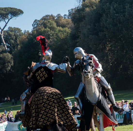 Men Wearing Armor Costumes Riding Horses On Field