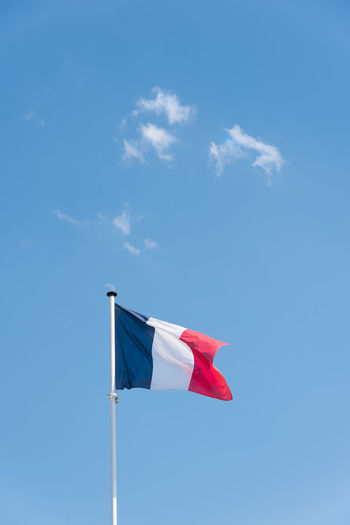 Low angle view of flag against blue sky. low angle view of french flag. the flag of france