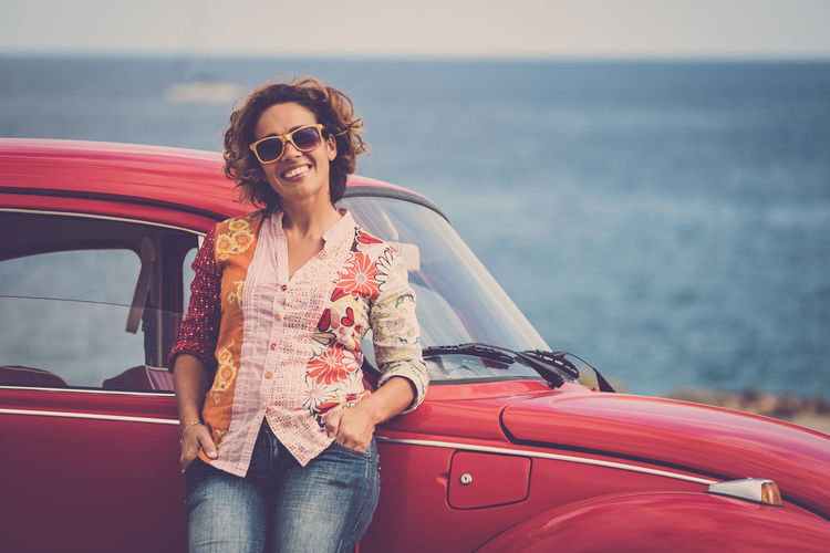 Beautiful caucasian middle age lady driver pose standing with a red legendary retro vintage car behind - ocean in background for travel and alternative lifesyle concept One Woman Only Females Enjoying Life Freedom Red Car Vintage Casual Clothing Caucasian Car Leisure Activity Mode Of Transportation Women Real People Transportation Sea One Person Lifestyles Smiling Motor Vehicle Three Quarter Length Glasses Adult Front View Sunglasses Red Fashion Mature Adult Horizon Over Water Outdoors Hairstyle Young Woman 40-44 Years Fashion People