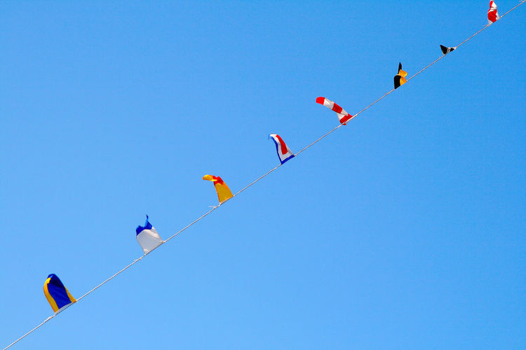 Low Angle View Of Colorful Flags Against Clear Blue Sky
