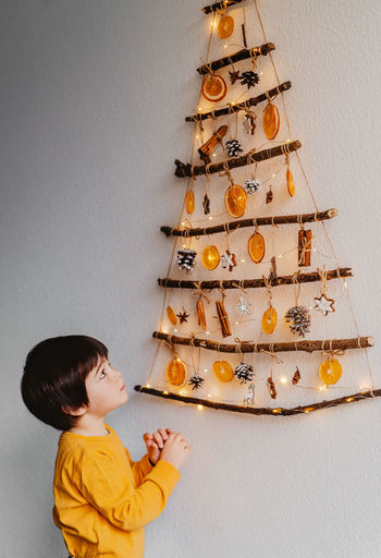 Boy looking at christmas tree against wall
