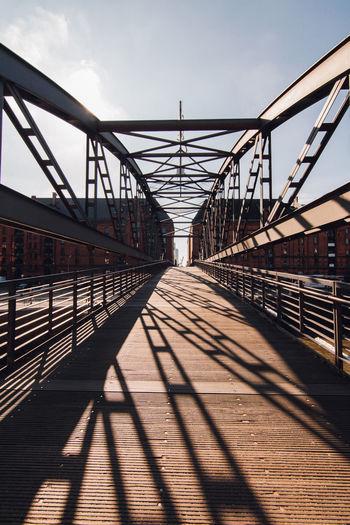 Metallic footbridge against sky during sunny day